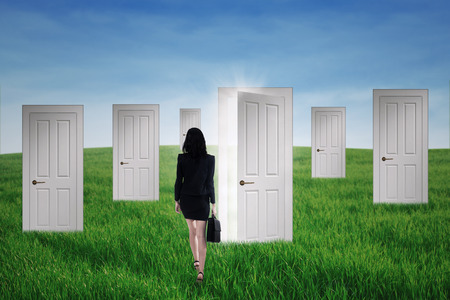 favorable: Young business woman walking into opportunity doors on the green field