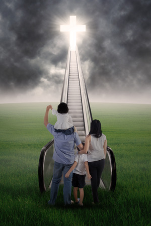 son of god: Christian family are standing on the stairs and looking at the bright Cross
