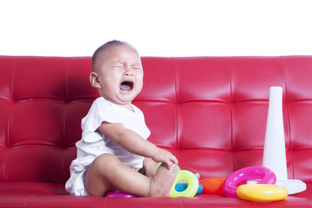 Little baby crying sitting on red sofa with toys