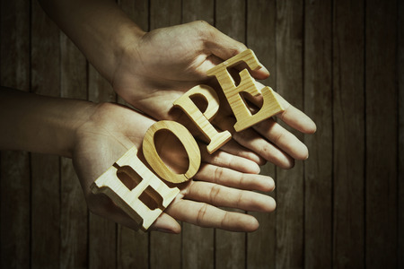 hope sign: Closeup of male hands holding a word of HOPE Stock Photo