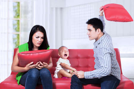 Scared baby sitting on the couch listening to parents argument  photo