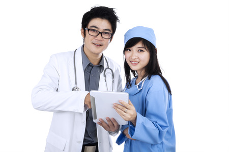 Young medical team checking results on digital tablet and smiling at camera. isolated on white background photo
