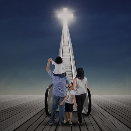 son of god: Asian family standing on the escalator and looking at bright cross Stock Photo