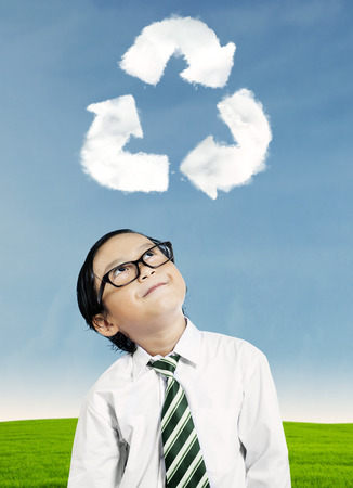 Little boy looking at recycle symbol above his head photo