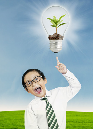 Excited little boy pointing at light bulb with plant over his head photo