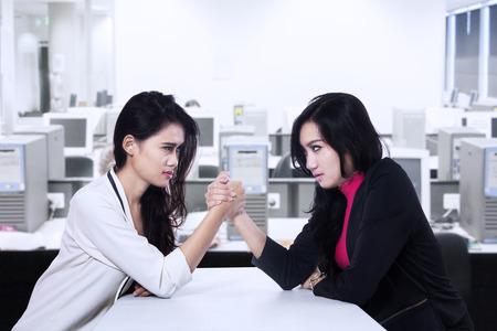 Businesswomen in arm wrestling gesture on working table during meeting photo