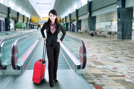 Business traveler in the airport standing with a luggage photo