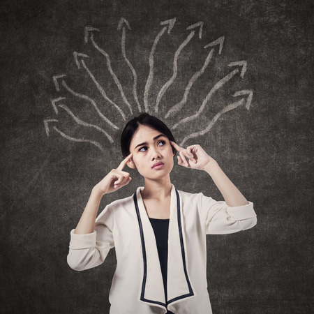 way of thinking: Businesswoman thinking with many arrows above her head Stock Photo