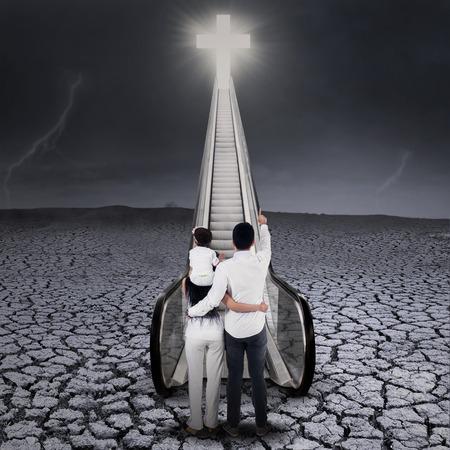 familia cristiana: Familia cristiana mirando brillante cruz, de pie sobre la tierra seca