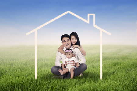 Happy family seated on the grass field and surrounded by home drawing Stock Photo
