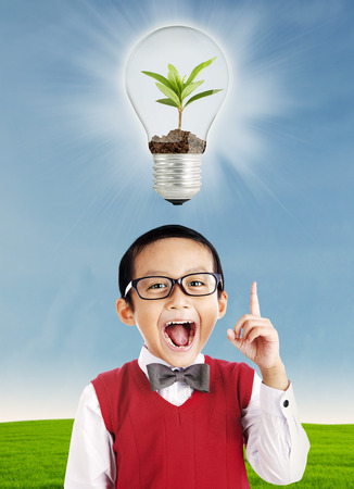 Happy school boy pointing at ecological concept over his head photo