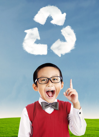 Happy school boy pointing at recycle symbol above his head photo