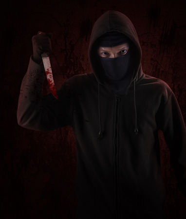 Dangerous hooded man standing in the dark and holding a bloody knife Stock Photo - 26134737