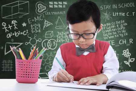 Asian student boy is writing on paper in classroom photo