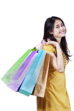 indonesian woman: Young beautiful woman with shopping bags isolated on white background