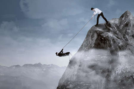 overcome a challenge: Portrait of businessman help his partner to climb the cliff by pulling her with a rope Stock Photo