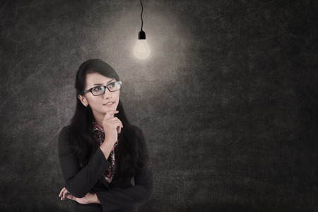asian business woman: Asian Business woman thinking under lightbulb in class