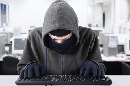 Computer hacker - Male thief stealing data from computer photo