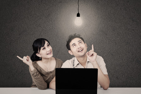 asian couple: Asian students looking at lit light bulb and laptop on grey background
