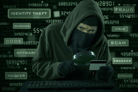 Internet Theft - a man wearing a balaclava looking at credit card code using magnifying glass photo