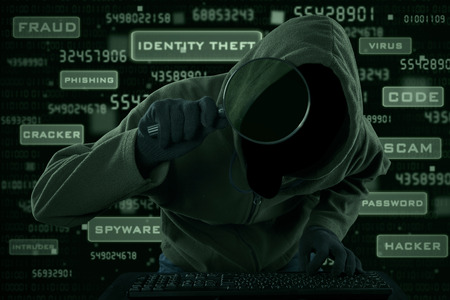 Internet Theft - a hooded man looking at computer screen using magnifying glass