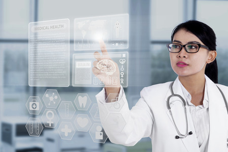 Female doctor touching medical interface with modern technology Imagens - 26135329