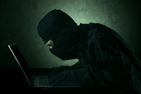 scammer: Hacker typing on a laptop and looking at computer screen