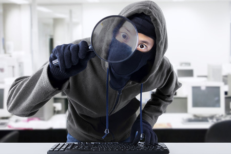 Computer hacker - Male thief stealing data from computer using magnifying glass photo