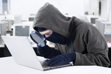 Internet Theft - a hooded man looking at computer screen using magnifying glass photo
