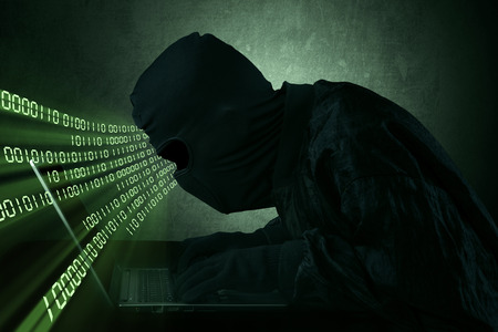 web scam: Hacker typing on a laptop with binary code in front of a computer screen Stock Photo