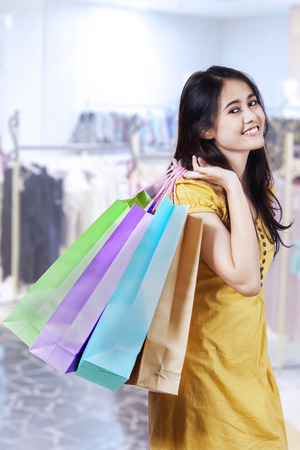 Young beautiful woman with shopping bags in shopping centre photo