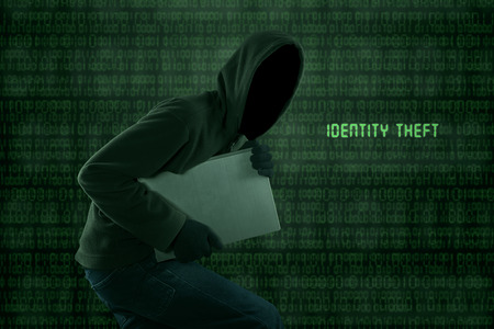Portrait of Identity theft stealing a laptop computer photo