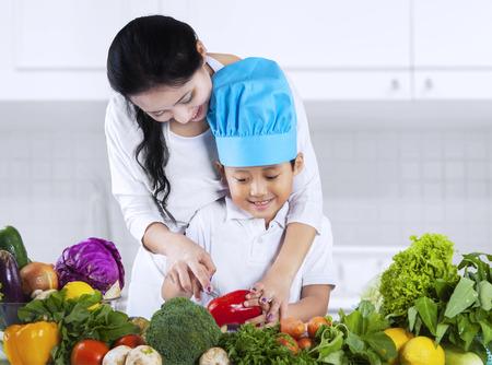 mujeres cocinando: Madre asi�tica est� ense�ando a su hijo para cortar vegetales en casa Foto de archivo