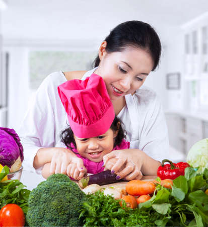 Asian mother is teaching her daughter to cut vegetable at home photo