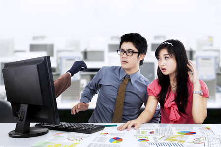 computer virus: Two young business people shocked of hackers hand on the screen Stock Photo