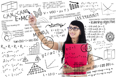 glassboard: Student woman writing formulas on glass board with marker Stock Photo