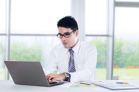 success focus: Portrait of young asian businessman typing on laptop computer.