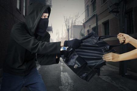 delincuencia: Ladrón joven robar el bolso de la mujer en la calle