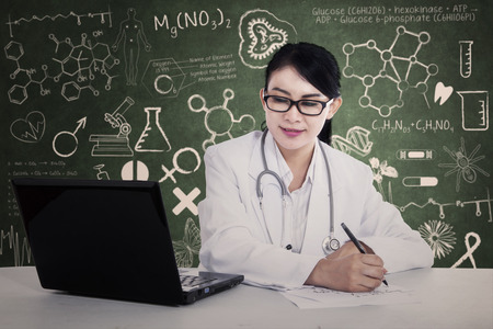Beautiful doctor is writing prescription at the laboratory photo
