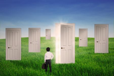 Business boy standing in front of opportunity doors - outdoor photo