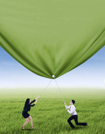 Two business people is pulling green banner on the meadow photo