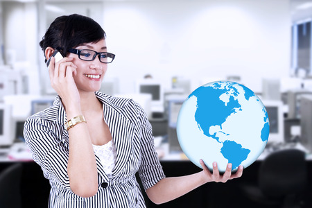 Businesswoman is calling and holding a blue world global at office photo