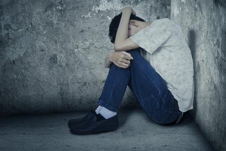 Jonge man zit op de hoek van de kamer met angst