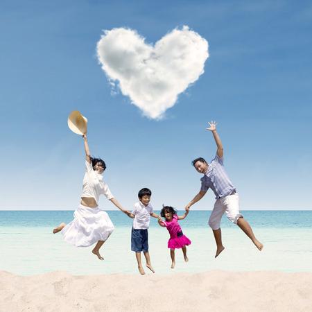 Glückliche asiatische Familie Springen unter Liebe Wolke am Strand