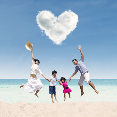Happy Asian family jumping under love cloud at beach Stock Photo