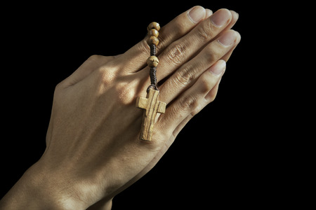 rosary beads: Hands holding rosary beads and cross while praying Stock Photo