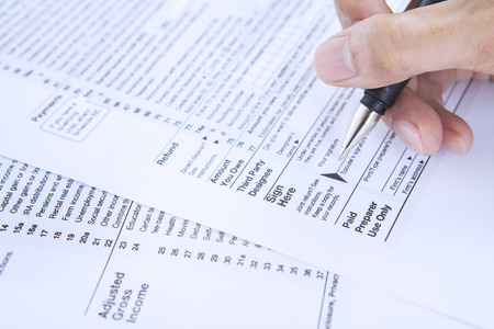 filling out: Closeup of businessman hand filling out a 1040 tax form
