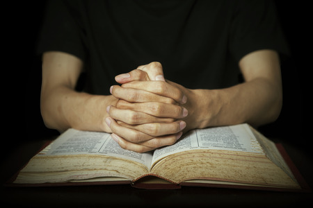 Closeup of hands praying on bible