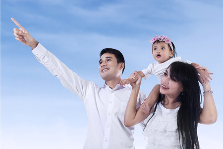 Young family pointing at copyspace - shooting outdoor photo