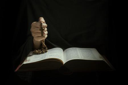 Handen die rozenkrans kralen en kruis tijdens het lezen van bijbel